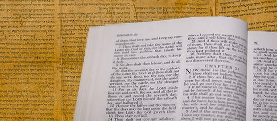 Picture of an open Bible in front of the Dead Sea Scrolls.